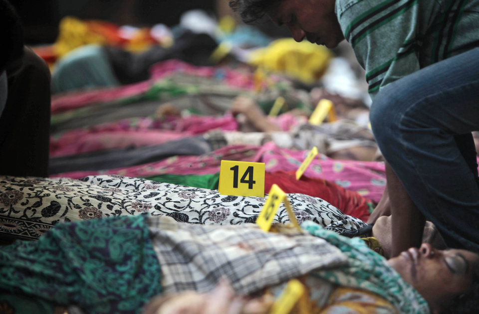 Bodies of victims of a building collapse lie numbered in a row in Savar, near Dhaka, Bangladesh, Wednesday, April 24, 2013. An eight-story building housing several garment factories collapsed near Bangladesh's capital on Wednesday, killing dozens of people and trapping many more under a jumbled mess of concrete. Rescuers tried to cut through the debris with earthmovers, drilling machines and their bare hands. (AP Photo/A.M.Ahad)
