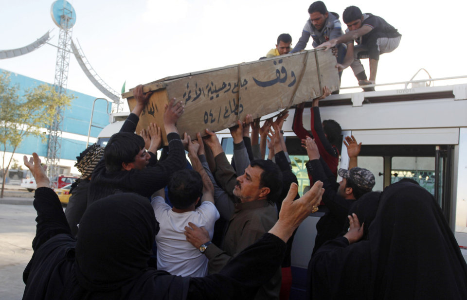 Photo - Family members of Hussein Abdullah, 22, who was killed in a car bomb attack, load his coffin onto a vehicle before transporting the coffin for burial in Najaf, 100 miles (160 kilometers) south of Baghdad, Iraq, Sunday, Feb. 17, 2013. A series of car bombs exploded within minutes of each other as Iraqis were out shopping in and around Baghdad on Sunday, killing and wounding scores of people, police said. (AP Photo/ Alaa al-Marjani)