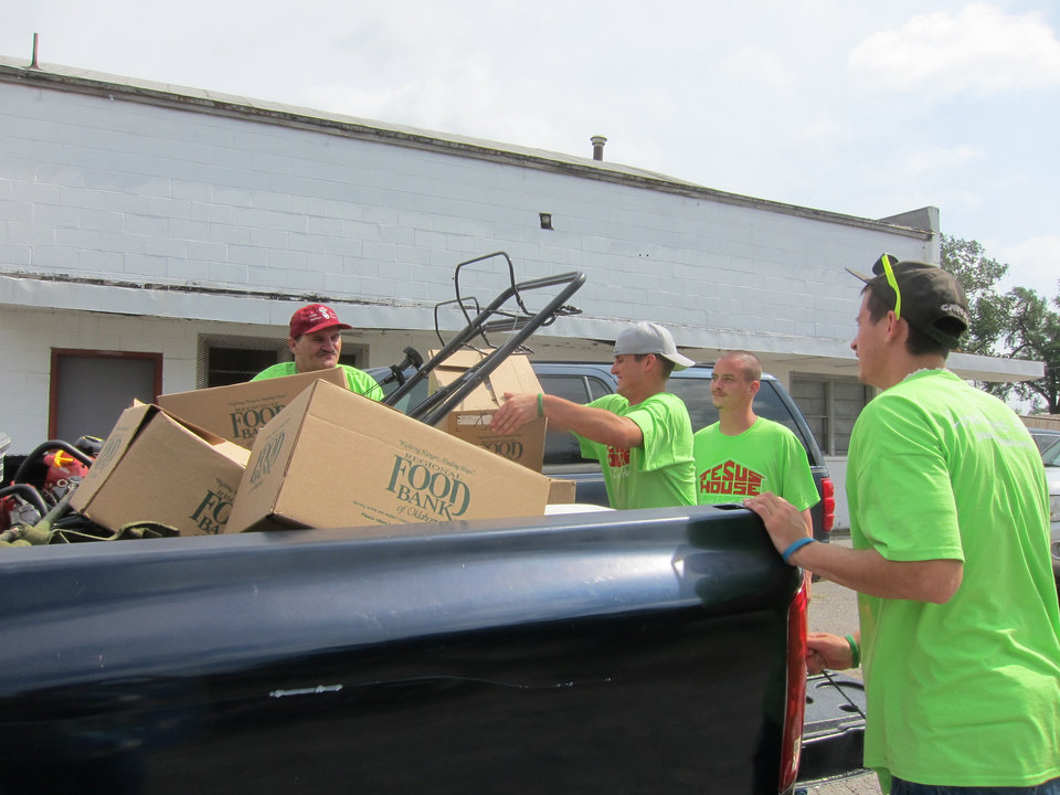 Photo -  Jesus House residents load a truck with lawn care equipment and food boxes as they prepare for the Jesus House's Adopt-A-Block program on Saturday mornings in the summer. Photo by Carla Hinton, The Oklahoman