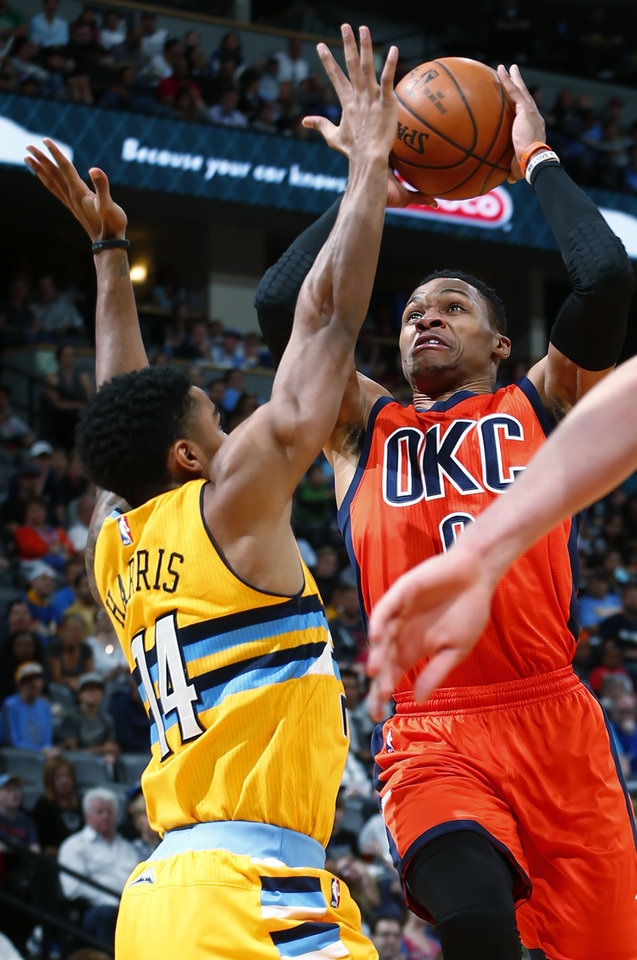 Photo - Oklahoma City Thunder guard Russell Westbrook (0) goes up for a shot against Denver Nuggets guard Gary Harris (14) during the first half of a basketball game, Sunday, April 9, 2017, in Denver. (AP Photo/Jack Dempsey)