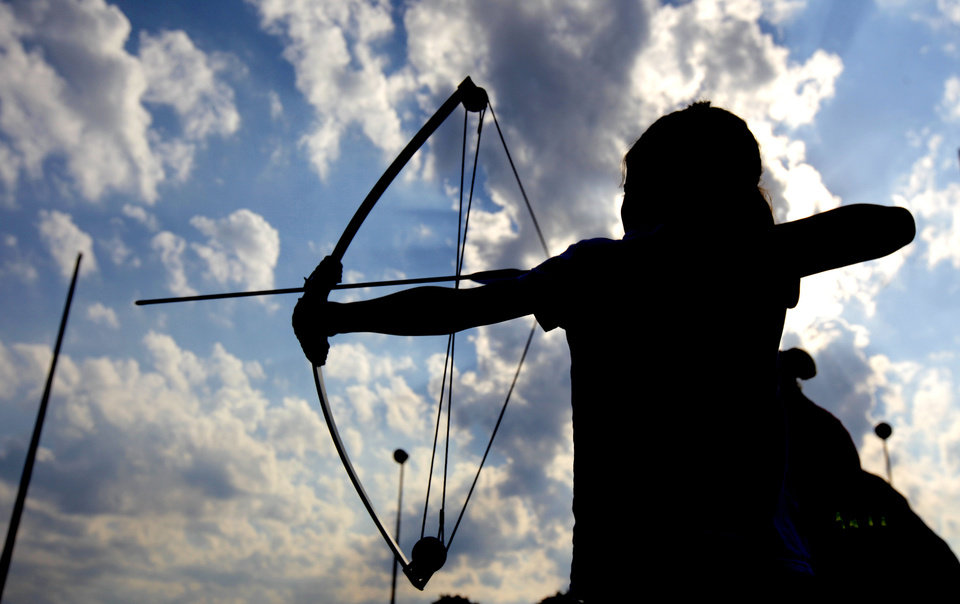 Photo - Gabrielle Parker, 9, of Enid takes aim during a Junior Olympic Archery Development Club shoot put on by the Trosper Archery Club on Saturday, August 24, 2013, at Trosper Park in Oklahoma City. Parker has come down from Enid about 4 times this summer and was one of over 60 participants, from beginners to intermediates, that took part in the shoot which takes place every Saturday. For $5 each person is supplied with equipment and instruction starting at 9am for beginners and 10am for intermediate shooters. Photo by Bryan Terry, The Oklahoman