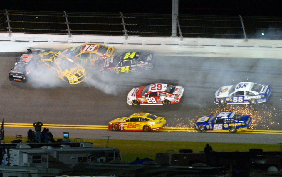 Photo - Denny Hamlin (11), Jimmie Johnson, second from left, Kyle Busch (18) and Jeff Gordon (24) collide in Turn 2 during the NASCAR Daytona Shootout auto race at Daytona International Speedway in Daytona Beach, Fla., Saturday, Feb. 16, 2013.(AP Photo/Phelan M. Ebenhack)