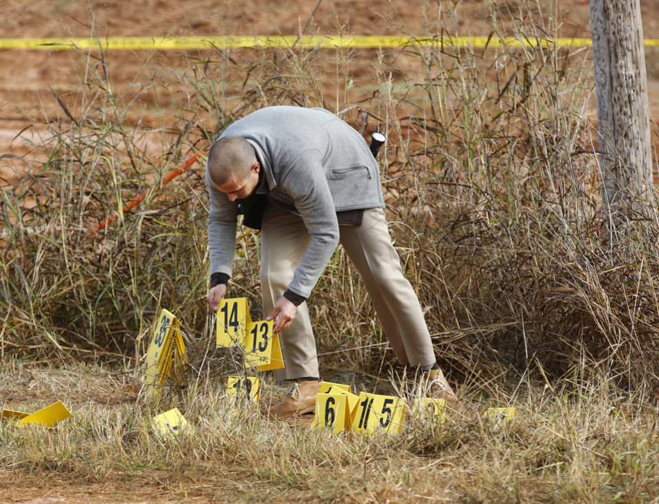 Photo - An OHP investigator collects evidence markers after his team completed their field investigation where county roads E 0870 and N 2130 intersect in Custer County on Monday, Oct. 31, 2016. Shots were fired at this location as troopers pursued double murder suspect Michael Vance, Jr. in a stolen vehicle before he was killed about 2 miles south of this location Sunday night in a gun battle with law officers. Photo by Jim Beckel, The Oklahoman