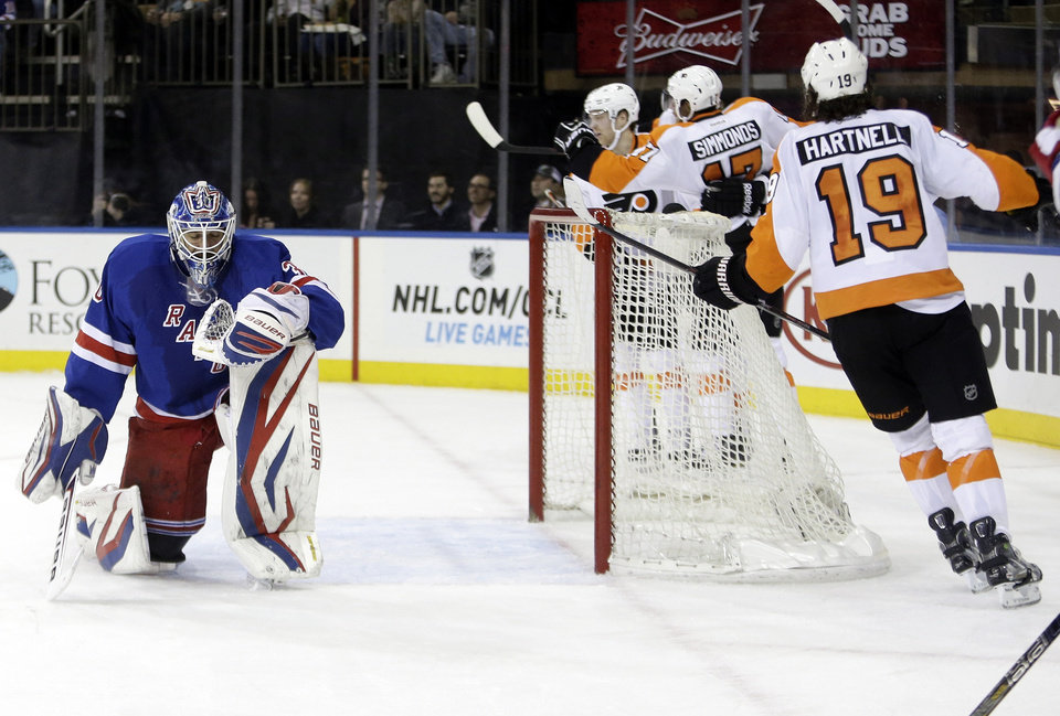 Photo - New York Rangers goalie Henrik Lundqvist, left, of Sweden, reacts as Philadelphia Flyers' Jakub Voracek, obscured, celebrates a goal with Wayne Simmonds, second from right, and Scott Hartnell, right, during the first period of an NHL hockey game Tuesday, March 5, 2013, in New York. (AP Photo/Frank Franklin II)