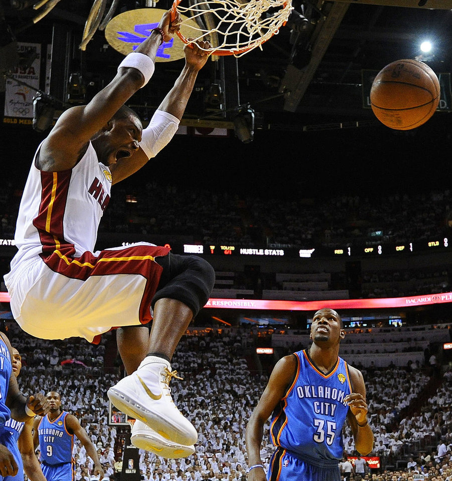 Miami Heat power forward Chris Bosh (1) dunks as Oklahoma City Thunder small forward Kevin Durant (35) looks on during the first half at Game 3 of the NBA Finals basketball series, Sunday, June 17, 2012, in Miami. (AP Photo/Larry W. Smith, Pool) ORG XMIT: NBA129