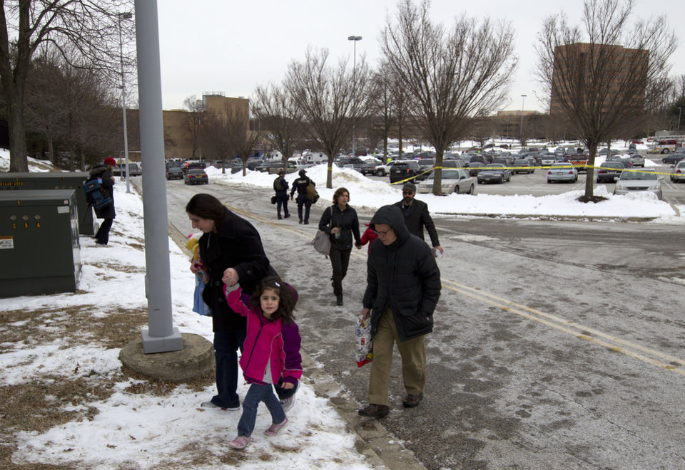 Photo - People are evacuated from the Mall in Columbia, Md., after a shooting at the mall on Saturday Jan. 25, 2014  in Howard County, Md. Police in Maryland say three people died Saturday in a shooting at a mall in suburban Baltimore, including the presumed gunman.  ( AP Photo/Jose Luis Magana)