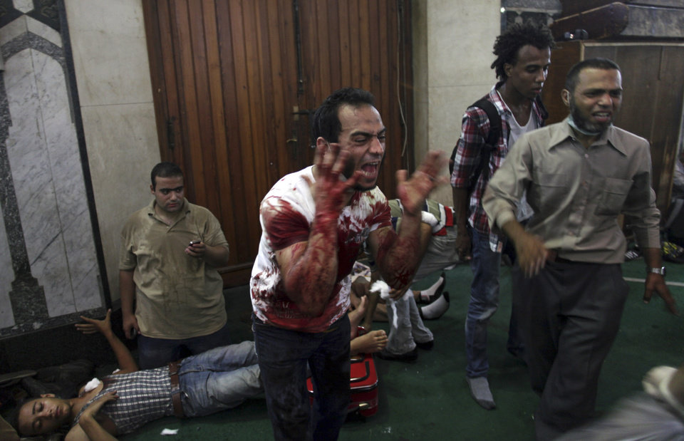Photo - An Egyptian man covered with blood shouts inside the Al-Fath mosque that is being used as a makeshift hospital and is receiving casualties from clashes between security forces and supporters of Egypt's ousted President Mohammed Morsi in Ramses Square, downtown Cairo, Egypt, Friday, Aug. 16, 2013. Gunfire rang out over a main Cairo overpass and police fired tear gas as clashes broke out after tens of thousands of Muslim Brotherhood supporters took to the streets Friday across Egypt in defiance of a military-imposed state of emergency following the country's bloodshed earlier this week. (AP Photo/Khalil Hamra)