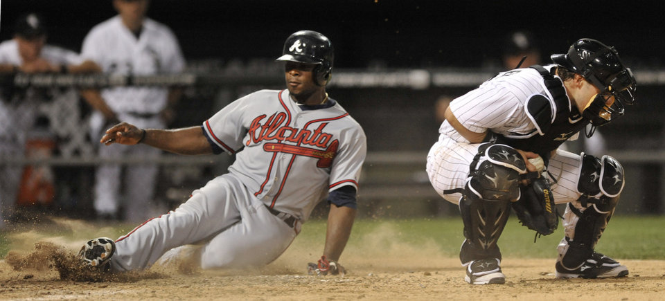 Photo - Atlanta Braves' Justin Upton left, slides into home plate safely as Chicago White Sox catcher Josh Phegley right, handles the throw during the ninth inning of an MLB baseball game in Chicago, Friday, July 19, 2013. Atlanta won 6-4. (AP Photo/Paul Beaty)