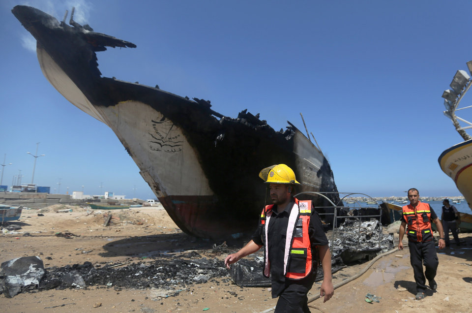 Photo - Palestinian firefighters walk around a boat hit in an missile strike at the port in Gaza City, Friday, July 11, 2014. Israel launched the Gaza offensive to stop incessant rocket fire that erupted after three Israeli teenagers were kidnapped and killed in the West Bank and a Palestinian teenager was abducted and burned to death in an apparent reprisal attack. The military says it has hit more than 1,100 targets already, mostly what it identified as rocket-launching sites, bombarding the territory on average every five minutes. (AP Photo/Hatem Moussa)