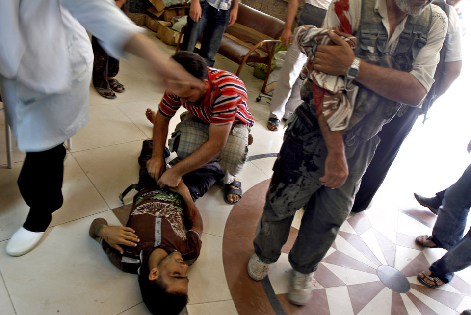 Photo -   Injured Syrian fighters receive treatment in a field hospital in Aleppo, Syria, Friday, Aug. 17, 2012. Rebel footholds in Aleppo have been the target of weeks of Syrian shelling and air attacks as part of wider offensives by President Bashar Assad's regime. Rebels have been driven from some areas, but the report of clashes near the airport suggests the battles could be shifting to new fronts. (AP Photo/ Khalil Hamra)