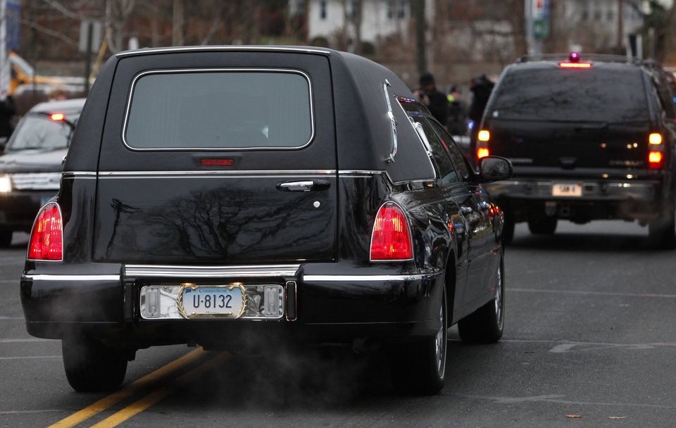 Photo - A hearse bears away the body of 6-year-old Noah Pozner after his funeral, Monday, Dec. 17, 2012, in Fairfield, Conn. Pozner was killed when a gunman walked into Sandy Hook Elementary School in Newtown Friday and opened fire, killing 26 people, including 20 children. (AP Photo/Jason DeCrow) ORG XMIT: CTJD115