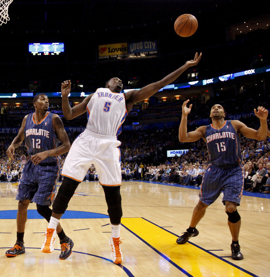 Photo - Oklahoma City's Kendrick Perkins (5) goes for the ball between Charlotte's Tyrus Thomas (12) and Gerald Henderson (15) during an NBA basketball game between the Oklahoma City Thunder and the Charlotte Bobcats at the Oklahoma City Arena, Friday, March 18, 2011. Photo by Bryan Terry, The Oklahoman