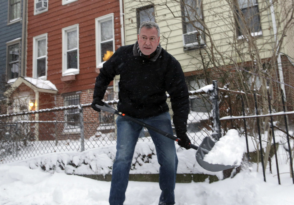 Photo - New York City Mayor Bill de Blasio shovels the sidewalk in front of his house in New York, Friday, Jan. 3, 2014. New York City public schools were closed Friday after up to 7 inches of snow fell by morning in the first snowstorm of the winter, and it the first test for the new mayor hours after he was sworn in. (AP Photo/Seth Wenig)