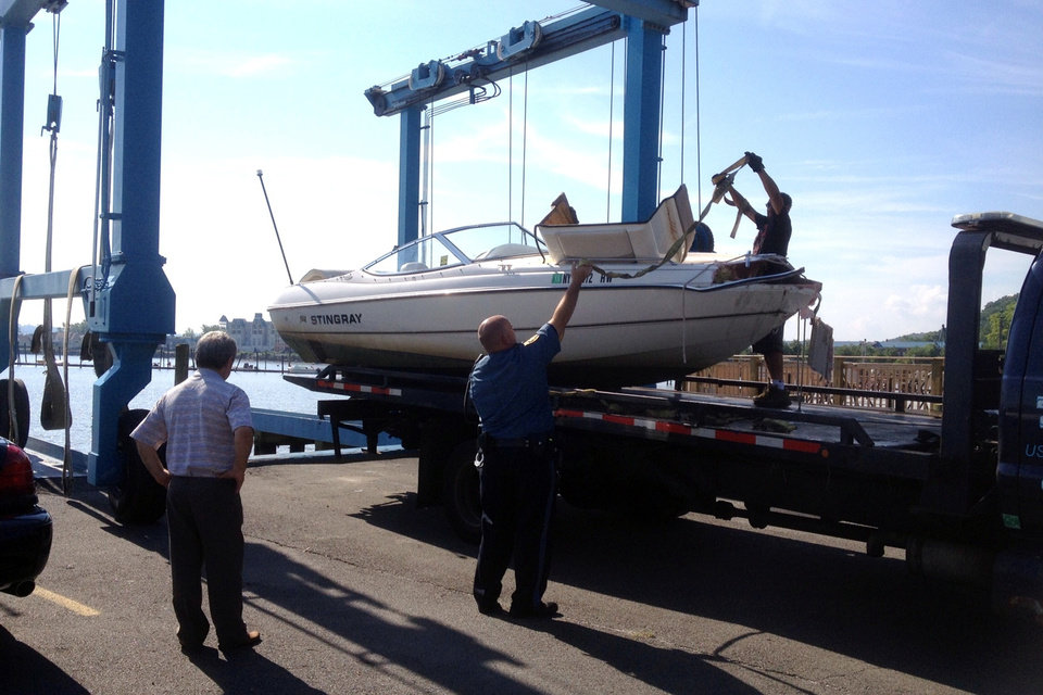 Officials remove the 21-foot Stingray powerboat involved in an accident on the Hudson River from the water in Piermont, N.Y, on Saturday, July 27, 2013. The Coast Guard says the recreational boat struck a barge near the Tappan Zee Bridge on Friday night, sending two people into the water who haven't been found and injuring four others. (AP Photo/The Journal News, Frank Becerra Jr.)