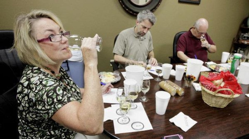 Photo - Wine judges Patty Held, Clayton Bahr and Bob Teeter judge wines in the wine competition at the Oklahoma State Fair. The second annual Wine Day at the fair will be today.  PAUL B. SOUTHERLAND - THE OKLAHOMAN