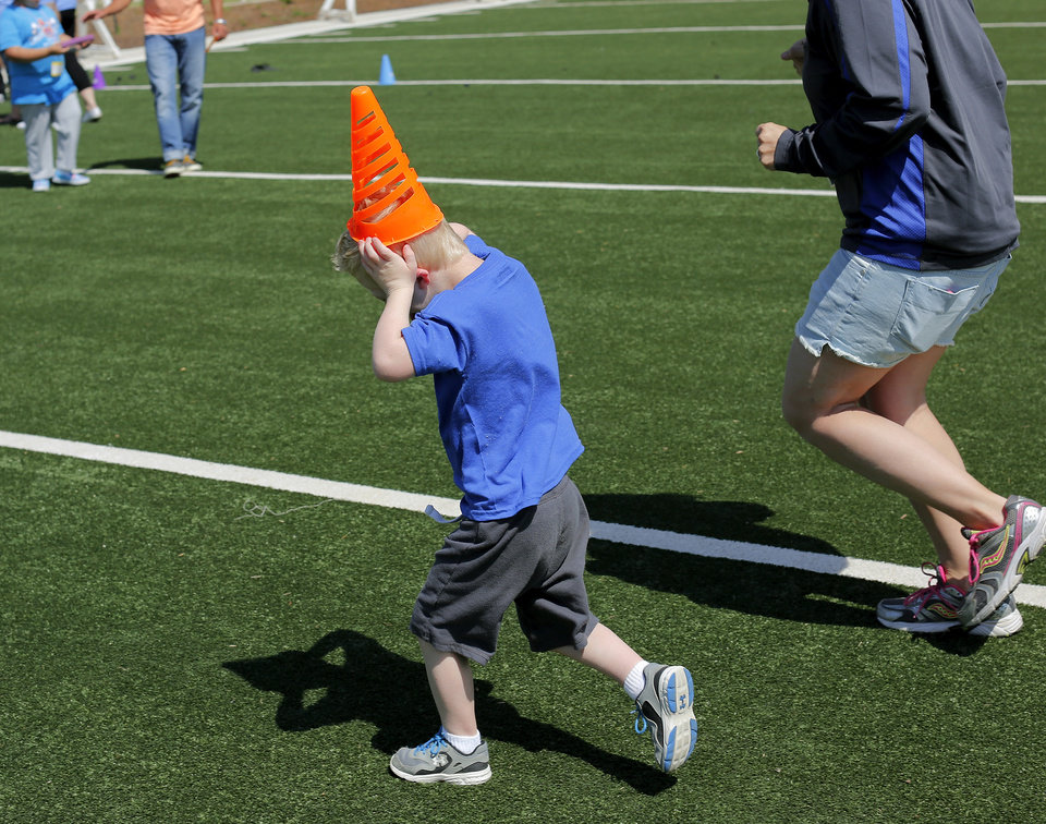 Photo - Jace Morton, 6, of Mooreland, runs a race after placing one of the course pylons atop his head in the 'Stars of the Future' area north of Boone Pickens Stadium on the campus of Oklahoma State University on Thursday, May 15, 2014.  Special Olympics athletes numbering in the thousands are competing in various events today and tomorrow  in Stillwater as the organization's 45th Annual Summer Games are held in Oklahoma this week.  Officials say more than 4,600 Special Olympics Oklahoma athletes have registered to compete this year, and thousands of volunteers are assisting during the three days of competitions.   This is the 31st year the summer games has been centered at Oklahoma State University.  Special Olympics is the world's largest sports organization for children and adults with intellectual disabilities, providing year-round training and competitions to more than 4.2 million athletes in 170 countries, according to their web site. Photo by Jim Beckel, The Oklahoman