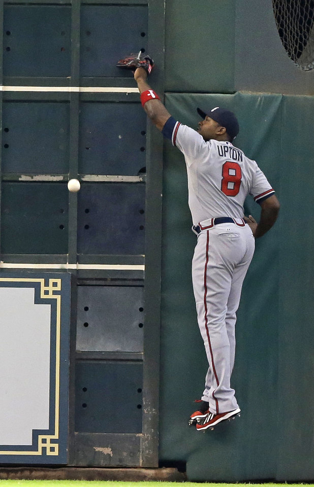 Photo - Atlanta Braves left fielder Justin Upton hits the wall and misses the ball for an RBI double for Astros' Jon Singleton in the first inning of a baseball game Thursday, June 26, 2014, in Houston. (AP Photo/Pat Sullivan)