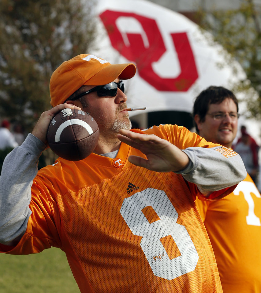 Photo - Tyler, Texas resident and Tennessee fan Jonathan Brown plays catch on camput before a college football game between the University of Oklahoma Sooners (OU) and the Tennessee Volunteers at Gaylord Family-Oklahoma Memorial Stadium in Norman, Okla., on Saturday, Sept. 13, 2014. Photo by Steve Sisney, The Oklahoman