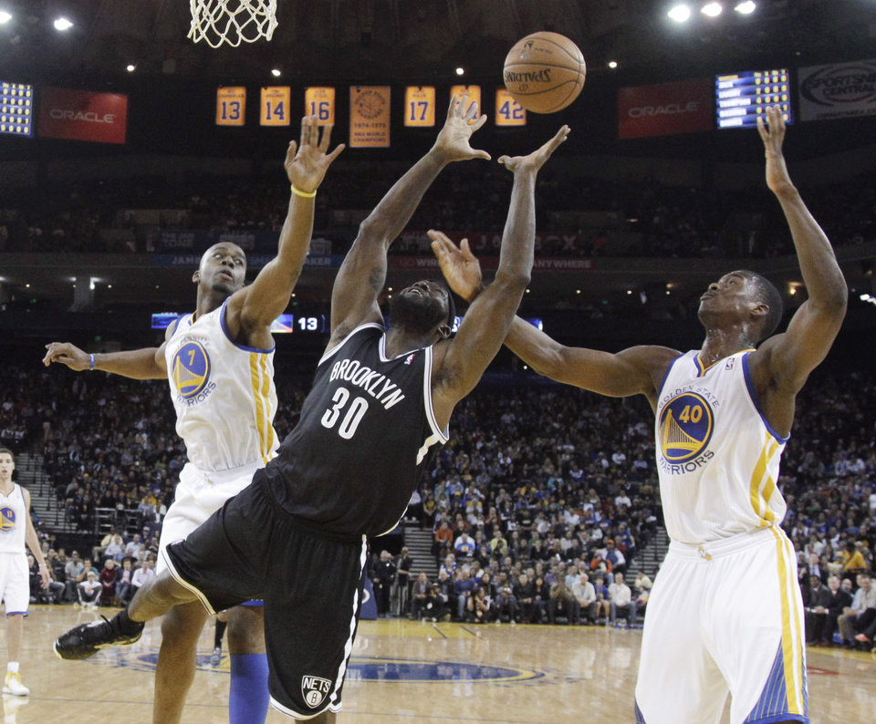 Photo -   Brooklyn Nets' Reggie Evans (30) grabs a rebound between Golden State Warriors' Carl Landry (7) and Harrison Barnes (40) during the first half of an NBA basketball game in Oakland, Calif., Wednesday, Nov. 21, 2012. (AP Photo/Marcio Jose Sanchez)