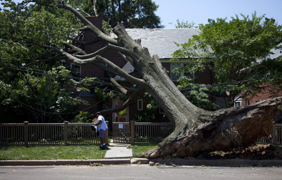 Photo -   Giovanny Alvarez, a letter carrier for the U.S. Postal Service, delivers mail to a residence in Washington, Monday, July 2, 2012 that damaged by the powerful storm that swept through the region Friday. (AP Photo/Evan Vucci)