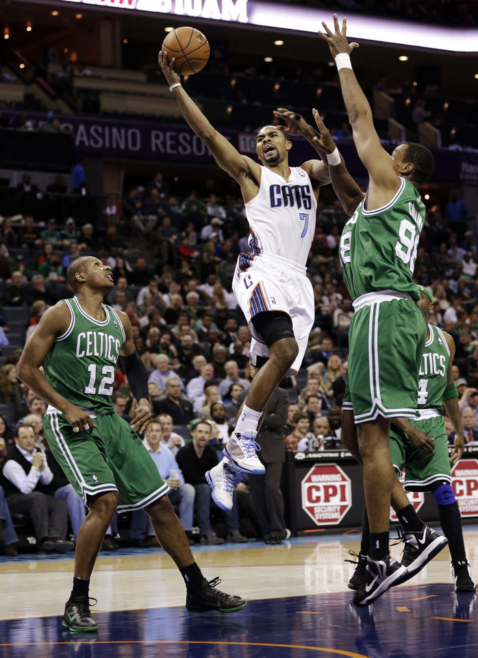 Photo - Charlotte Bobcats' Ramon Sessions (7) drives between Boston Celtics' Leandro Barbosa (12) and Jason Collins (98) during the first half of an NBA basketball game in Charlotte, N.C., Monday, Feb. 11, 2013. (AP Photo/Chuck Burton)