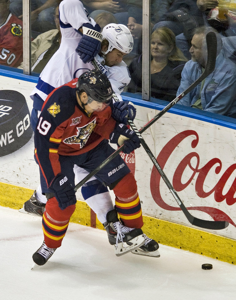 Photo - Florida Panthers forward Scottie Upshall (19) battles Tampa Bay Lightning's Pierre-Cedric Labrie during the first period of an NHL preseason hockey game Thursday, Sept. 26, 2013, in Estero, Fla. (AP Photo/Steve Nesius)