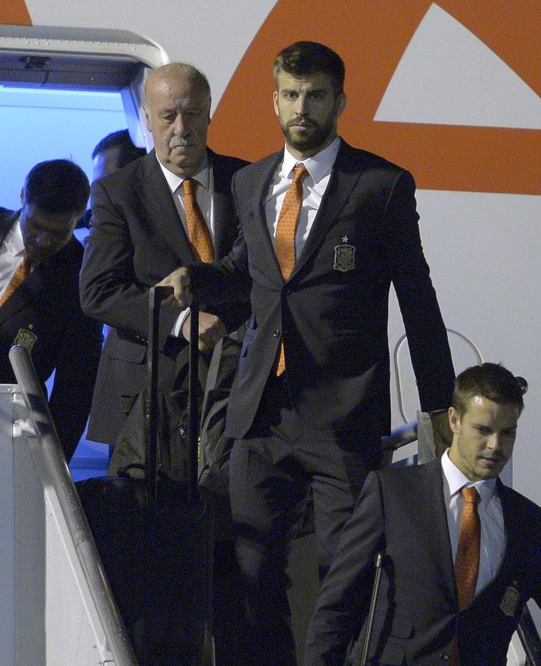 Photo - Head coach Vicente Del Bosque of Spain, left, and Gerard Pique, second from left, arrive at the international airport Alfoso Pena in Curitiba, Brazil, Sunday, June 8, 2014, Spain's national soccer team arrived in Curitiba to continue their preparations for the upcoming 2014 World Cup. (AP Photo/Manu Fernandez)