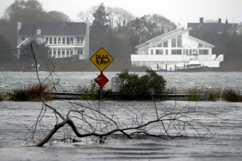 Photo -   A downed limb lies in a flooded street as Hurricane Sandy approaches, Monday, Oct. 29, 2012, in Center Moriches, N.Y. Hurricane Sandy continued on its path Monday, as the storm forced the shutdown of mass transit, schools and financial markets, sending coastal residents fleeing, and threatening a dangerous mix of high winds and soaking rain.  (AP Photo/Jason DeCrow)