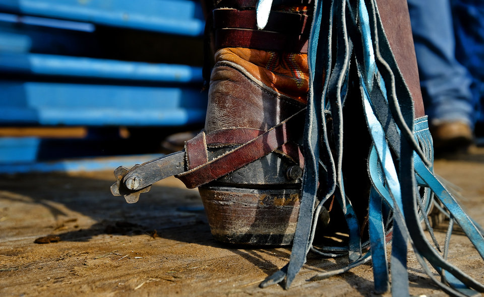 A saddle bronc rider wears his spurs before his run during day three of the International Youth Finals Rodeo at the Shawnee Expo Center in Shawnee, Okla. Tuesday, July 10, 2012.   Photo by Chris Landsberger, The Oklahoman