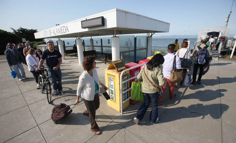 Photo - Commuters board the San Francisco Bay Ferry at the Harbor Bay terminal in Alameda, Calif., on Tuesday, July 2, 2013. The BART strike is in its second day and bargaining talks have not resumed. (AP Photo/The Contra Costa Times, Jane Tyska)