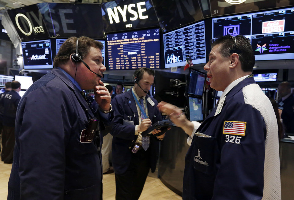 Photo - Traders John Santiago, left, and William McInerney, right, work on the floor of the New York Stock Exchange, Tuesday, May 13, 2014. The Standard & Poor's 500 index crossed above 1,900 for the first time Tuesday as investors assessed news on retail sales. DirecTV gained on reports that the AT&T is poised to buy the company for nearly $50 billion. (AP Photo)