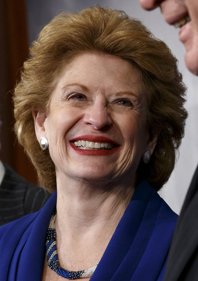 Photo - FILE - In this Feb 4, 2014 file photo, Senate Agriculture Committee Chair Sen. Debbie Stabenow, D-Mich., is seen during a news conference on Capitol Hill in Washington, Tuesday, Feb. 4, 2014, after Congress gave its final approval to a sweeping five-year farm bill. When President Barack Obama comes to East Lansing on Friday to sign the Farm Bill, it will put attention on how research schools such as Michigan State University will be one of the big beneficiaries of the nearly $100 billion-a-year measure — even if the millions it represents is comparatively small. And scientists are breathing a sigh of relief that funding will continue flowing, along with money for new efforts, after years of political wrangling. (AP Photo/J. Scott Applewhite)