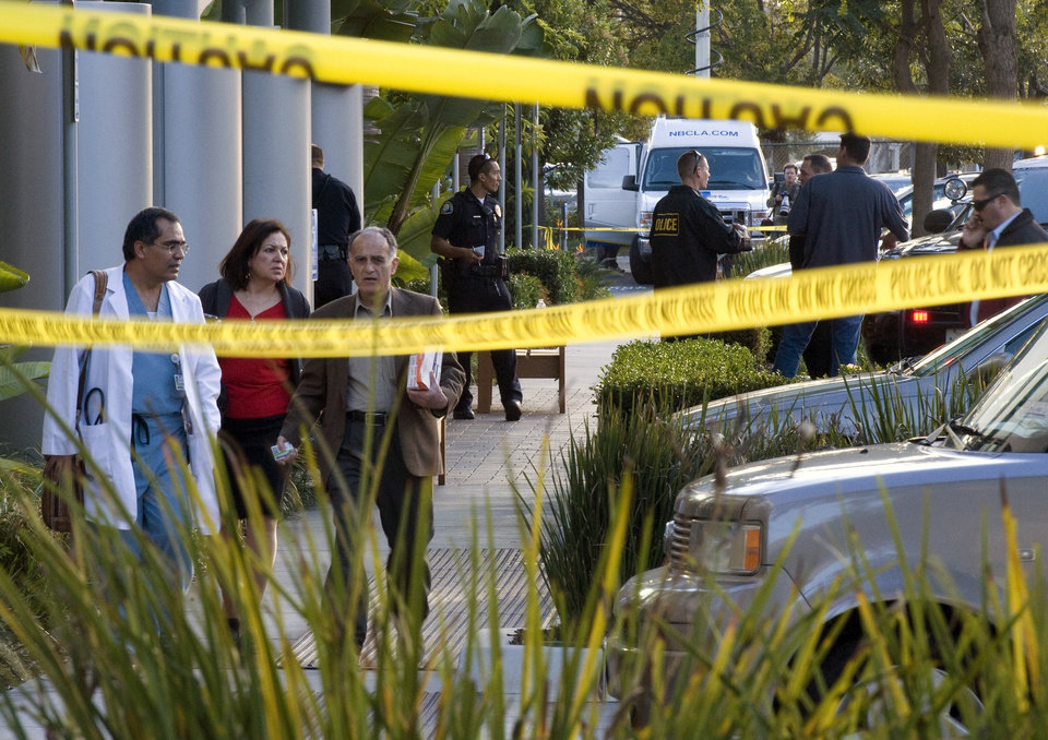 Police investigate as medical personnel exit the scene outside a medical office near Hoag Hospital where shots were fired on Monday, Jan. 28, 2013, in Newport Beach, Calif. Police say a doctor has been shot and killed and a man is in police custody. (AP Photo/The Orange County Register, Joshua Sudock)
