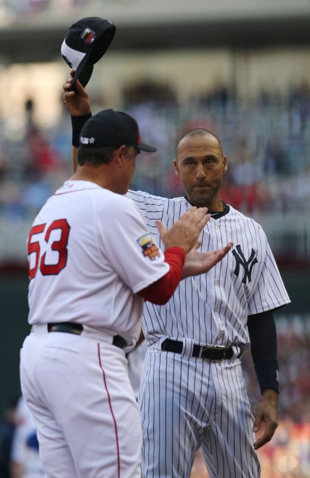 Photo - American League shortstop Derek Jeter, of the New York Yankees, waves to the crowd as American League Manager John Farrell, of the Boston Red Sox, left, looks on before the MLB All-Star baseball game, Tuesday, July 15, 2014, in Minneapolis. (AP Photo/Jim Mone)