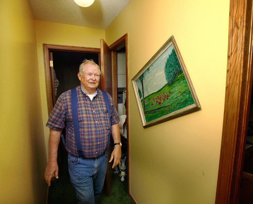 Photo - Joseph Reneau walks past a crooked painting on the wall in an upstairs hallway after two earthquakes damaged his home and its contents. An earthquake late Saturday night caused extensive damage to the two-story ranch style home of Joseph and Mary Reneau near the community of Sparks in Lincoln County.  Contents inside their home were damaged earlier Saturday when a earthquake was struck the same area.  The Reneaus have lived in their house for 25 years. Photo by Jim Beckel, The Oklahoman  ORG XMIT: KOD