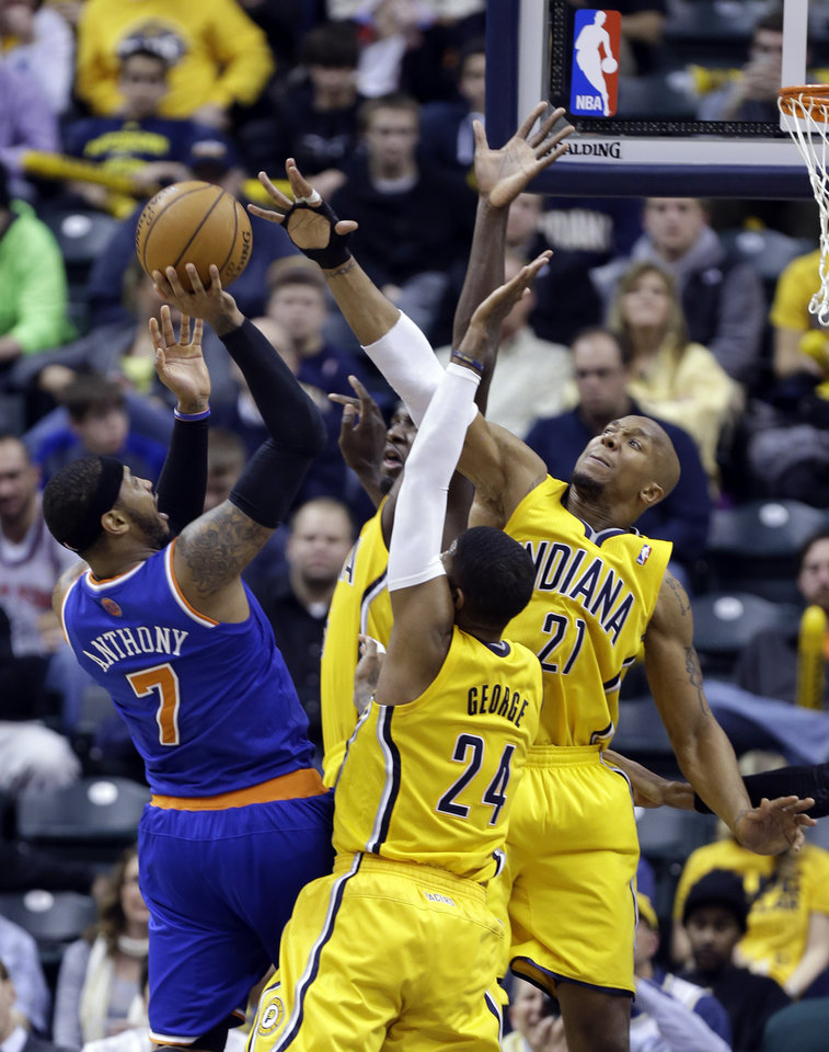 Photo - New York Knicks forward Carmelo Anthony, left, tries to shoot over Indiana Pacers' Paul George (24), David West (21) and Roy Hibbert during the second half of an NBA basketball game in Indianapolis, Thursday, Jan. 16, 2014. The Pacers defeated the Knicks 117-89. (AP Photo/Michael Conroy)
