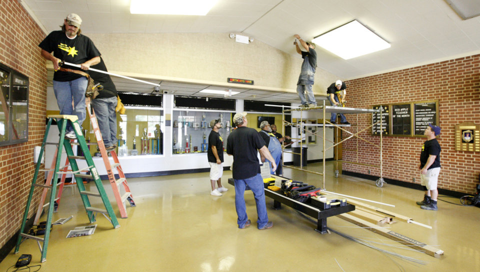 Photo - Maintenance workers prepare to install a ceiling during a school beautification project called