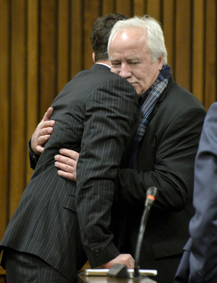 Photo - Oscar Pistorius, left, gets a hug from his estranged father Henk Pistorius, right, in court at his murder trial in Pretoria, South Africa, Friday, Aug. 8, 2014. The chief defense lawyer for Oscar Pistorius, Barry Roux is delivering his final arguments in the athlete's murder trial and focusing on allegations that police mishandled evidence at the house where Pistorius fatally shot girlfriend Reeva Steenkamp. (AP Photo/ Herman Verwey, Pool)