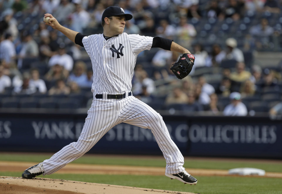 Photo - New York Yankees relief pitcher David Phelps delivers against the Pittsburgh Pirates during the first inning of a baseball game, Saturday, May 17, 2014, in New York. (AP Photo/Julie Jacobson)