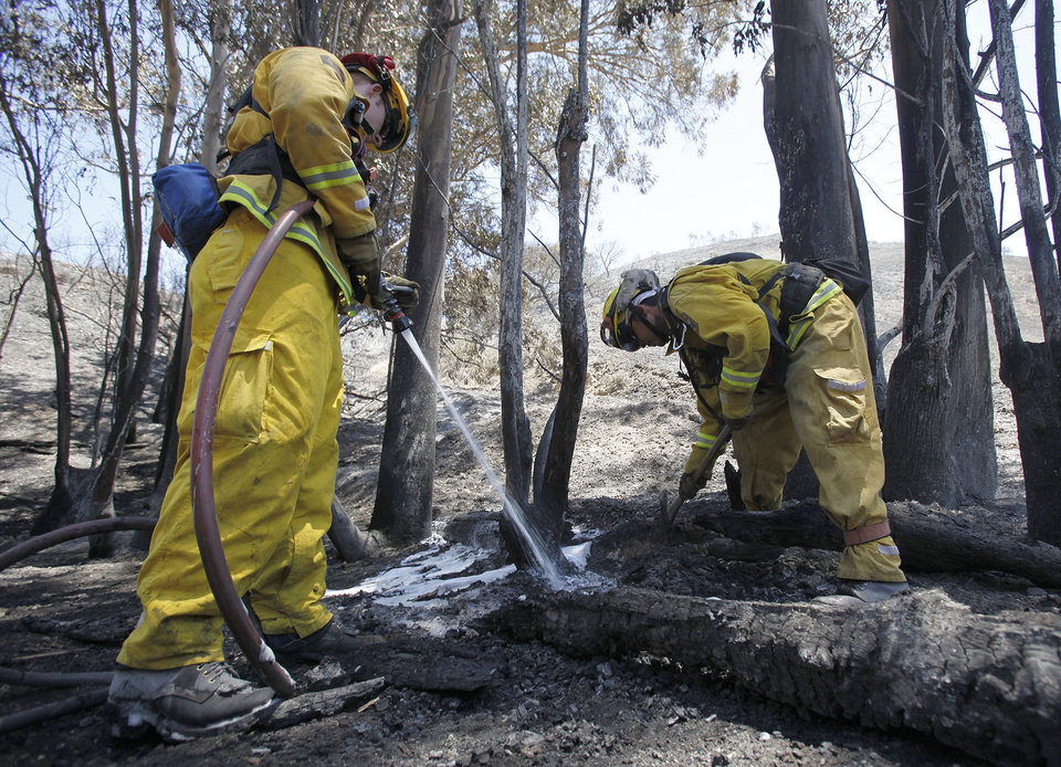 Photo - California firefighters from Fresno Jordan Meyer, left, and Martin Perez extinguish a hot spots along Miguelito Road, Wednesday, May 14, 2014, near Lompoc, Calif. Thousands were asked to evacuate their homes in Carlsbad after the blaze erupted at about 10:34 a.m. Wednesday and spread through rapidly heavy brush before jumping into residential areas. (AP Photo/The Santa Maria Times, Daniel Dreifuss)