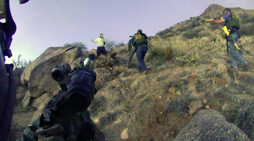 Photo - This March 16, 2014 photo, taken from a video camera worn by an Albuquerque Police Department officer, shows police in a standoff with a homeless man in the Albuquerque foothills just before they fired six shots at him. Police say James Boyd, 38, who later died at a hospital, refused to drop a knife and had threatened to kill officers. His death sparked an FBI investigation and a violent street protest that forced the city to call out riot officers. (AP Photo/Albuquerque Police Department)