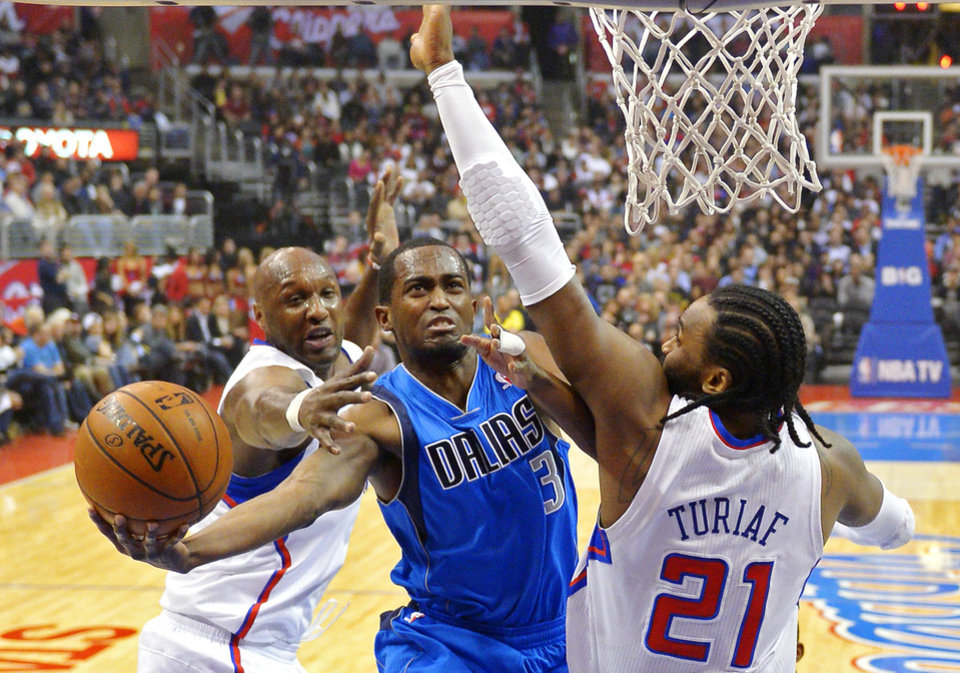 Dallas Mavericks guard Rodrigue Beaubois (3), of France, shoots as Los Angeles Clippers forward Lamar Odom, left, and center Ronny Turiaf (21), of France, defend during the first half of their NBA basketball game, Wednesday, Jan. 9, 2013, in Los Angeles. (AP Photo/Mark J. Terrill)