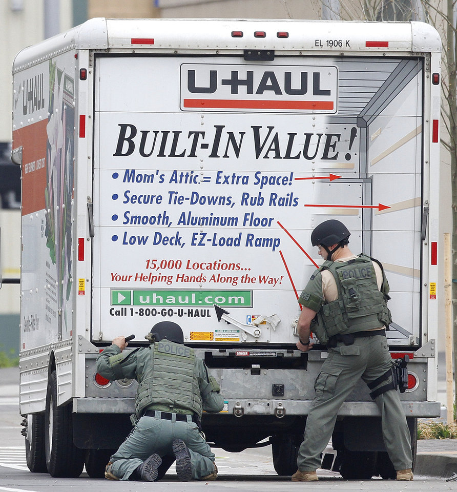 Photo - BOMB SCARE: Members of the Oklahoma City Police Bomb Squad search a U-Haul truck parked on Walker Avenue in downtown Oklahoma City , Wednesday April 17, 2013. Photo By Steve Gooch, The Oklahoman ORG XMIT: OKC1303121532440650