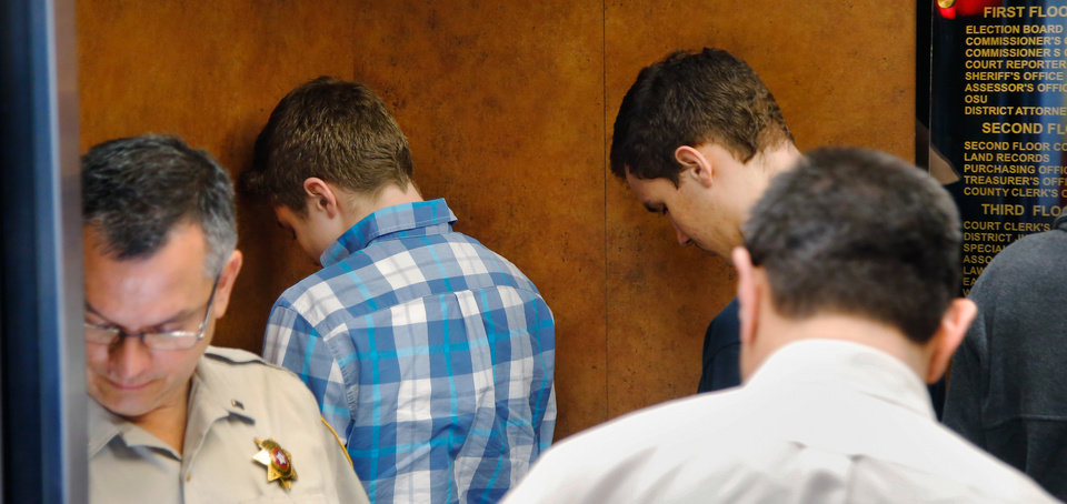 Photo - Hunter Oren Matthews, wearing plaid shirt, 17, and Chase Denton Smith, 16, turn their faces to the back wall of a third floor courthouse elevator as they are being escorted to the Garvin County Sheriff's office. They entered pleas of not guilty to charges stemming from an alleged sexual assault last month on two teammates on the school's wrestling team. Four students from Norman North High School were arraigned before Special Judge Trisha  Misak in the Garvin County Courthouse in downtown Pauls Valley Tuesday afternoon, Feb. 2, 2016. They are accused of rape by instrumentation. Photo by Jim Beckel, The Oklahoman.
