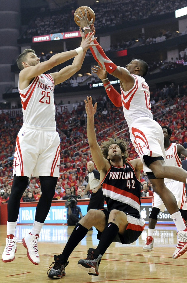 Photo - Houston Rockets Chandler Parsons (25) and Dwight Howard (12) grab a rebound over a falling Portland Trail Blazers' Robin Lopez (42) in the first half of Game 5 of an opening-round NBA basketball playoff series Wednesday, April 30, 2014, in Houston. (AP Photo/Pat Sullivan)