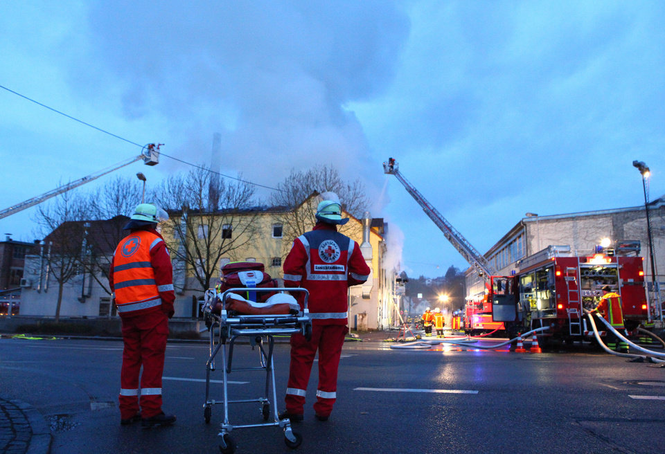 Photo - Rescuers stand near a house in Backnang,  Germany Sunday March 10, 2013.  An early-morning fire on Sunday at the apartment building in southwestern Germany left seven people dead, six of them children, police said.  Authorities were alerted to the blaze in Backnang, a town near Stuttgart, at 4.30 a.m. Police said in a statement that they believe the fire broke out in a second-floor apartment, and said that their investigation is focusing on a heater in the apartment. (AP Photo/dpa, Benjamin Beytekin)