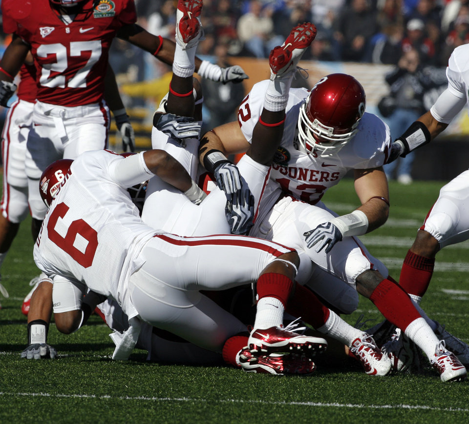 Photo - Desmond Jackson (6) and Austin Box (12) tackle Michael Thomas (3) during the first half of the Brut Sun Bowl college football game between the University of Oklahoma Sooners (OU) and the Stanford University Cardinal on Thursday, Dec. 31, 2009, in El Paso, Tex.   Photo by Steve Sisney, The Oklahoman