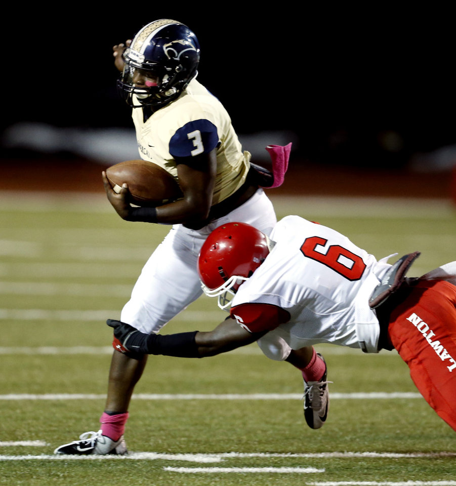 Photo - Lawton's Mahlik Hanna brings down Jaelon Walker (3) as the Southmoore Sabercats play the Lawton High School Wolverines in high school football on Friday, Oct. 11, 2013, in Moore, Okla. Photo by Steve Sisney, The Oklahoman