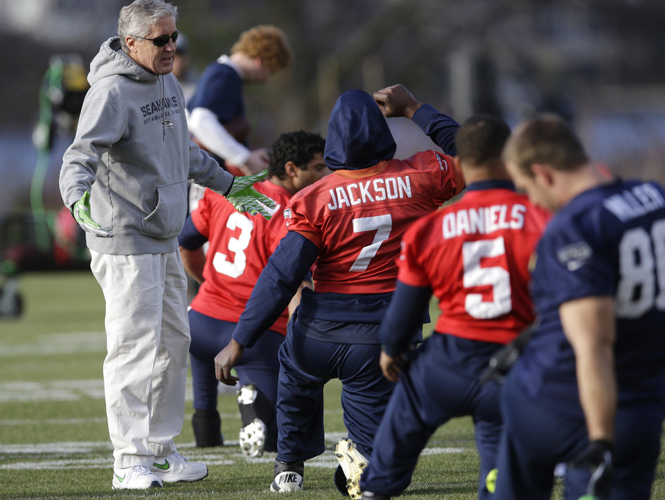 Photo - Seattle Seahawks coach Pete Carroll, left, talks with backup quarterback Tarvaris Jackson (7) during stretching drills before NFL football practice, Friday, Jan. 3, 2014, in Renton, Wash. Seattle plays at home in a playoff game on Jan. 11. (AP Photo/Ted S. Warren)