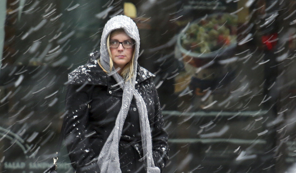Photo - A morning commuter, bundled against the cold, watches the snow begin to fall in Washington early Wednesday, March 6, 2013. The Mid-Atlantic region is expected to get 6 to 10 inches of snow. (AP Photo/J. David Ake)